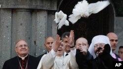El papa Francisco y el arzobispo católico griego Sviatoslav Shevchuk (derecha) liberan palomas blancas durante la visita del pontífice a la Basílica de Santa Sofía en Roma, el domingo, 28 de enero de 2018.