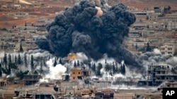 شام کے شہر کوبانی پر اتحادی فورسز کے فضائی حملے کے بعد دھوئیں کے بادل بلند ہو رہے ہیں۔ فائل فوٹو