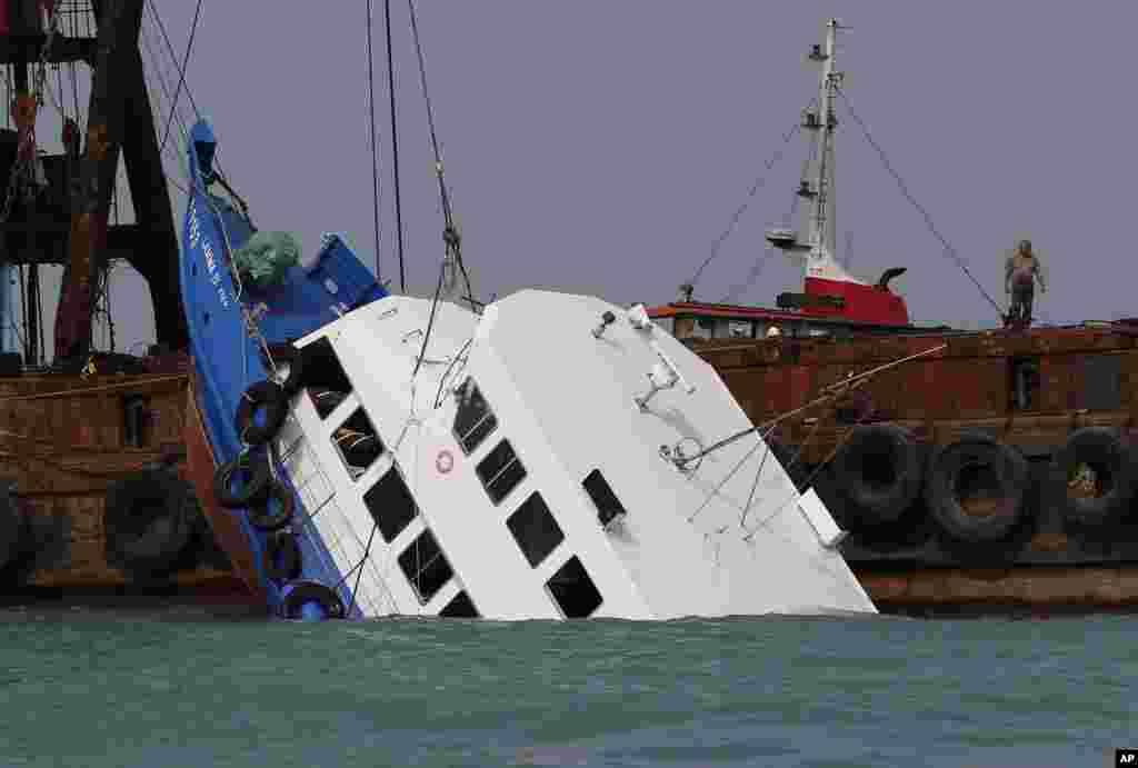 Officials check on a half submerged boat after it collided Monday night near Lamma Island, off the southwestern coast of Hong Kong Island, October 2, 2012.