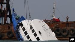 Para petugas berusaha mengangkat kapal ferry yang tenggelam di Pulau Lamma, Hong Kong (2/10).