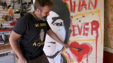 Photo of Manny Oliver smashing a painting with a hammer