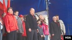 共产党议员卡申(身穿红衣)同俄共领袖久加诺夫(讲话者)在5月1日莫斯科共产党游行集会上(美国之音白桦拍摄)