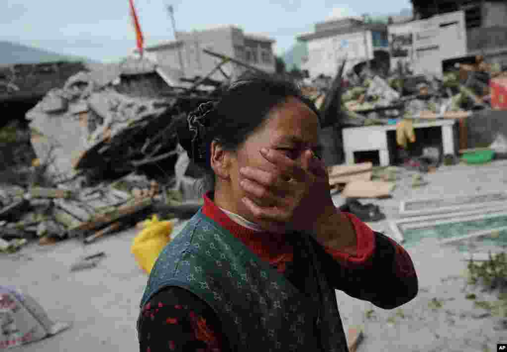 A village woman reacts after her house was damaged by an earthquake in Lushan county, Ya'an, southwest China's Sichuan province, Apr. 20, 2013.