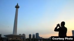 Seorang pengunjung nampak seperti siluet saat memotret Monumen Nasional, Jakarta (Foto: dok). Berbagai organisasi kemasyarakatan keagamaan atau laskar umat Islam di Solo akan bergabung dalam aksi demo di Jakarta, Jumat mendatang (4/11).