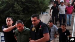 FILE - Members of Turkey's armed forces are escorted by police at the court house in Mugla, a Mediterrenean city of Turkey, for their suspected involvement in an attempted July 2016 coup.