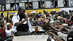Malian-born Ivorian comic and presidential candidate Adama Dolo greets people from an open-deck car during an election campaign in Abidjan, 20 Oct. 2010