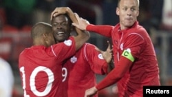 Canada's Simeon Jackson (L) and Kevin McKenna (R) celebrate with teammate Tosaint Ricketts after he scored on Cuba in the first half of their 2014 FIFA World Cup qualifying soccer match in Toronto, October 12, 2012.