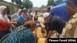 Warga di sebuah desa di Cibarusah, Bekasi di Jawa Barat sedang mengantri untuk mendapatkan air bersih. Kekeringan telah mengurangi pasokan air bersih untuk warga di wilayah tersebut. (Courtesy Photo/Firman Forsil)