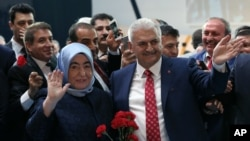 Binali Yildirim, Turkey's current Transportation Minister and founding member of the AKP, Turkey's governing party, and his wife Semiha Yildirim salute supporters during party congress in Ankara, May 22, 2016.