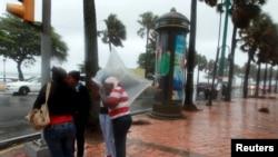 Warga berhujan-hujanan di pinggir jalan di Santo Domingo.