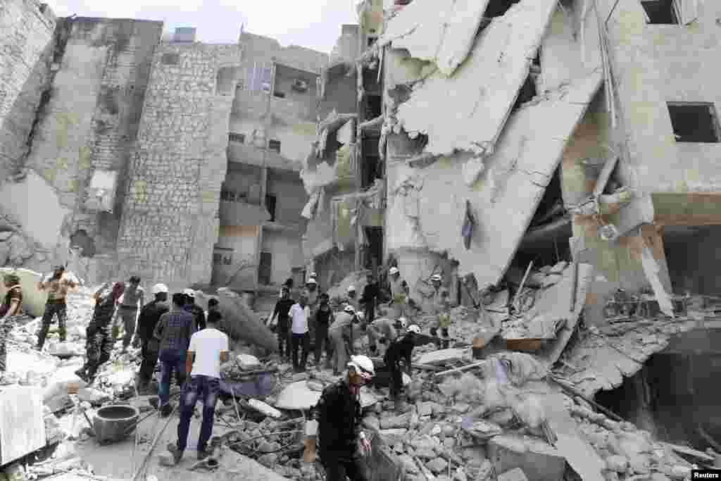 Rescue workers, rebel fighters and civilians search for survivors at a site hit by what activists said was a barrel bomb dropped by forces loyal to President Bashar al-Assad, al-Qarlaq, Aleppo, May 29, 2014.