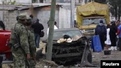 Tentara, warga setempat dan angora tim forensik berdiri di depan tempat ledakan di desa Yesus Tepactepec, dekat ibukota negara bagian Tlaxcala (15/3).