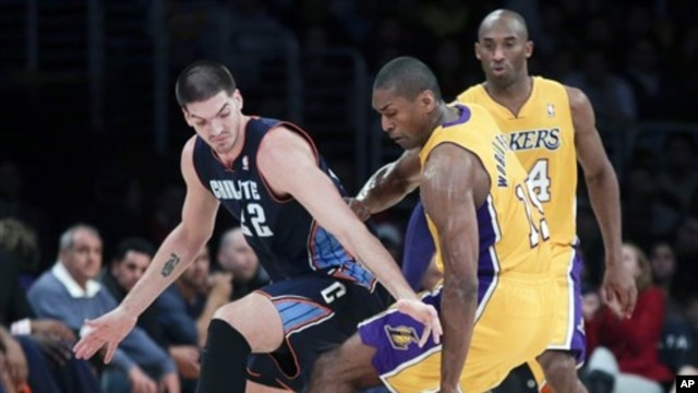 Pemain Lakers dari Los Angeles, Metta World Peace (tengah) merebut bola dari pemain Charlotte Bobcats, Byron Mullens (kiri). Kobe Bryant mengamati dari pinggir lapangan dalam setengah putaran pertama pertandingan bola basket NBA di Los Angeles, Selasa, 18 Desember 2012 (AP Photo/Chris Carlson).