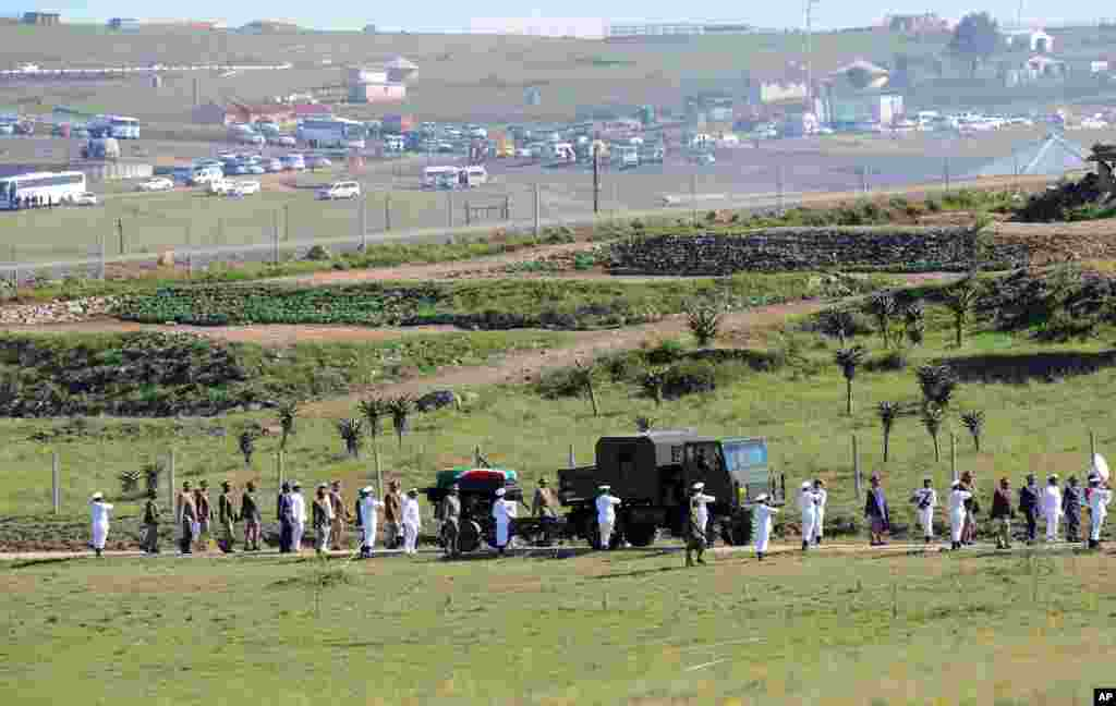 The casket of former South African president Nelson Mandela is carried on a gun carriage toward the dome for his funeral service in Qunu, Dec. 15, 2013.