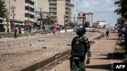 Un officier de police regarde les manifestants, alors qu'ils continuent de lancer des pierres et de bloquer les routes lors de manifestations de masse après la publication des résultats préliminaires à Conakry le 23 octobre 2020.