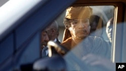 Libyan leader Moammar Gadhafi about to get into a car in Tripoli, Libya, Sunday, April 10, 2011.