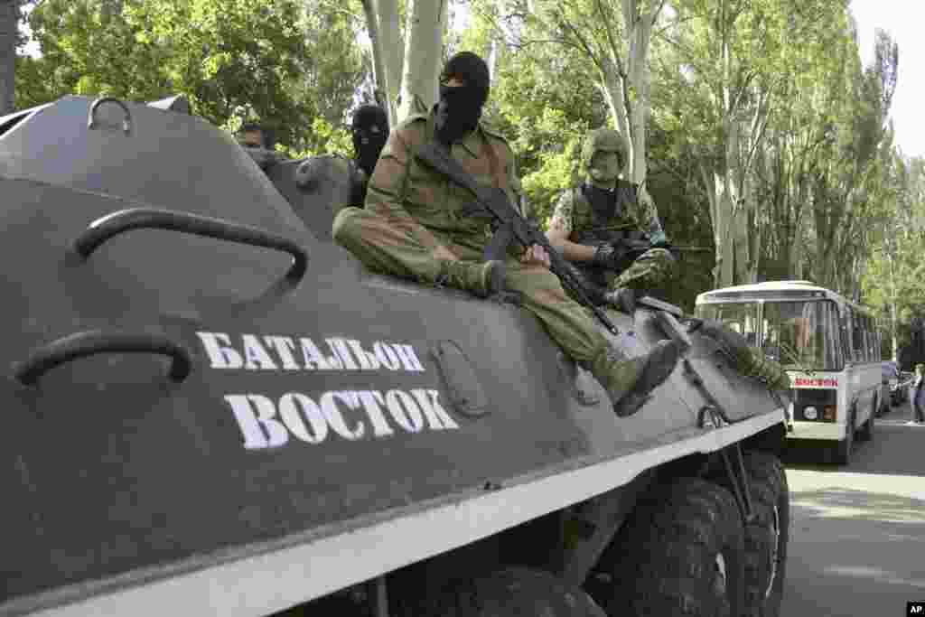 "Pro-Russian gunmen sit on an armored personnel carrier with the words read ""Battalion Vostok (East) "" as they patrol in Donetsk, Ukraine, May 20, 2014."