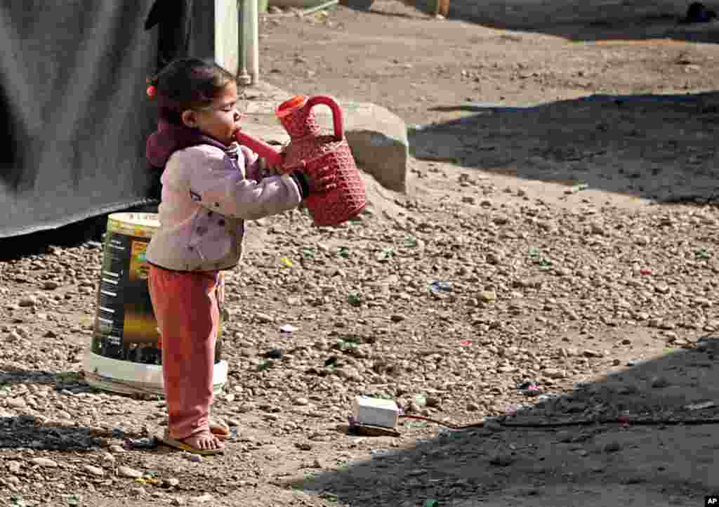 آب خوردن دختربچه از آفتابه در کمپ آوارگان در عراق