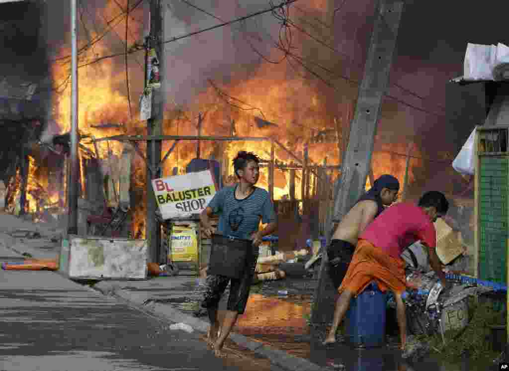 Residents put out fire that gutted several homes while government troopers continue their assault at Muslim rebels in Zamboanga city in southern Philippines.