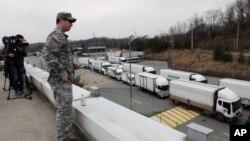 Binh sĩ Mỹ đứng xem xe cộ Hàn Quốc trở về từ khu công nghiệp Kaesong từ văn phòng Di trú và Hải quan gần khu phi quân sự, ngày 28/3/2013.