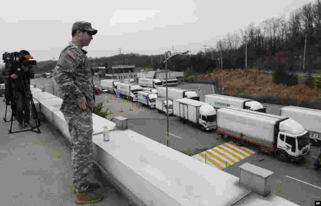 South Korean vehicles return from a joint industrial complex at the North Korean city of Kaesong as a U.S. Army soldier watches at the customs, immigration and quarantine office, near the Demilitarized Zone, March 28, 2013.