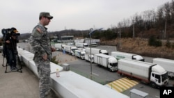 Seorang tentara Amerika mengamati arus kendaraan Korea Selatan yang kembali dari kompleks perindustrian di Kaesong, Korea Utara dari kantor pabean, imigrasi dan karantina dekat zona demiliterisasi (28/3).