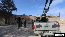 Các chiến binh Lực lượng Dân chủ Syria đi bên ngoài một nhà tù mà theo họ, thuộc về các chiến binh Nhà nước Hồi giáo, ở thị trấn al-Shadadi, tỉnh Hasaka, Syria, ngày 26/2/2016.