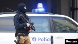 FILE - A Belgian special forces police officer stands guard outside a courthouse as Paris attacks suspect Salah Abdelslam remains in police custody, in Brussels, Belgium, April 7, 2016.