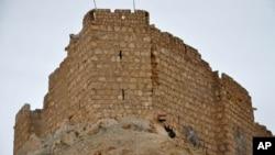 叙利亚官方通讯社发布的图片显示叙利亚军人在古迹前面手持国旗(2016年3月27日)
