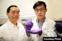 James Lee, Ph.D., left, examines a silicone chip with Junfeng Shi at The Ohio State University College of Engineering. Lee, who led a team of engineers who designed the chip, collaborated with Ohio State Wexner Medical Center on this study to reprogram skin cells to become other types of cells. (Photo courtesy of The Ohio State University Wexner Medical Center)