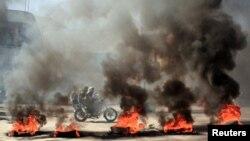 یمن کے شہر تعز میں ایک موٹرسائیکل سوار سٹرک پر مظاہرین کی طرف سے سڑک پر جلائی آگ کے درمیان سے گزر رہا ہے ملک میں خراب معاشی صورت حال کے خلاف مظاہرے ہو رہے ہیں۔ 27 ستمبر 2021