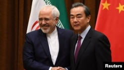 Menteri Luar Negeri Iran Mohammad Javad Zarif (kiri) dan Menlu China Wang Yi sebelum pertemuan di di Beijing, Senin (5/12).