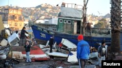 People recover items from destroyed houses next to a ship dragged by the waves after a earthquake hit areas of central Chile, in Coquimbo city, north of Santiago, Chile, September 17, 2015. (REUTERS/Mauricio Ubilla)
