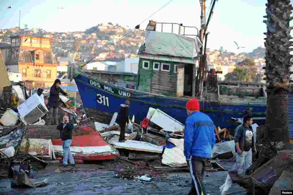 People recover items from destroyed houses around a ship pushed onto land by the waves of a tsunami after an earthquake hit areas in Coquimbo city, north of Santiago, Chile.