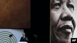 U.S. President Barack Obama, at podium delivers his speech at the 16th Annual Nelson Mandela Lecture at the Wanderers Stadium in Johannesburg, South Africa, July 17, 2018.