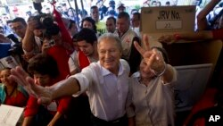 Vice President Salvador Sanchez, presidential candidate for the ruling Farabundo Marti National Liberation Front (FMLN) and his wife Margarita Villalta pose for photos after voting at a polling station in San Salvador, El Salvador, Feb. 2, 2014.