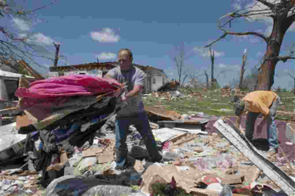Marcos Plunkett, a la izquierda, con la ayuda de Allen Souto, a la derecha, rescata algunas de prendas de vestir entre los escombros de su casa de Phil Campbell, Alabama.