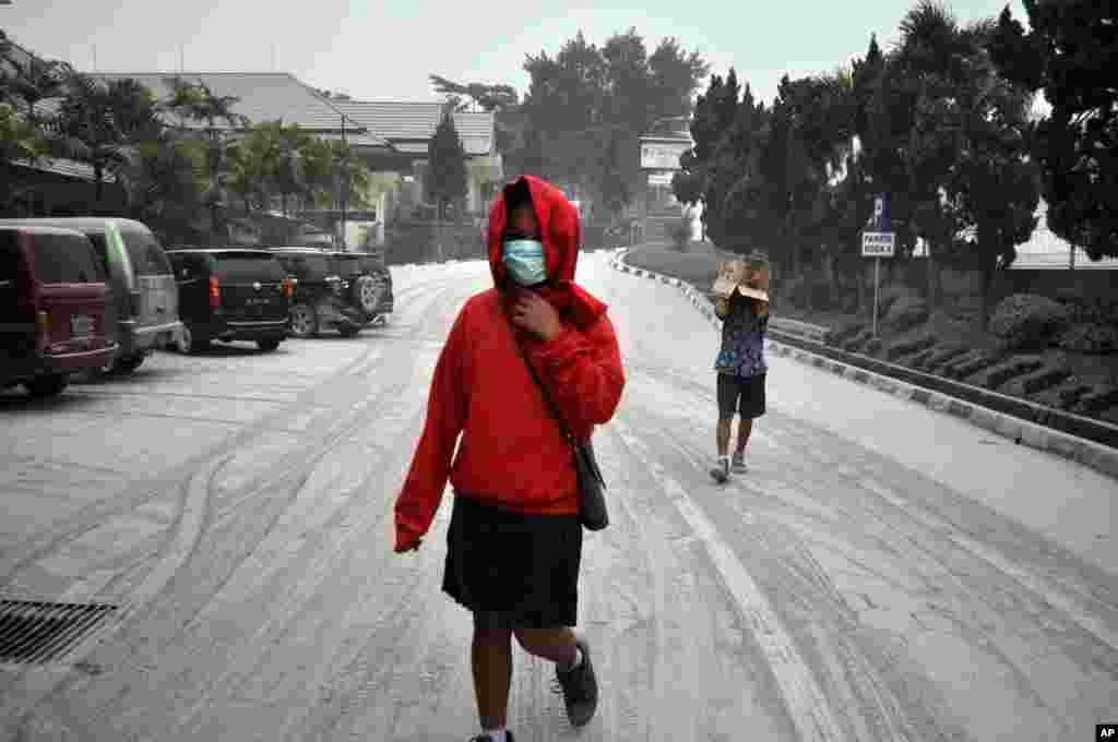 Học sinh Indonesia đi bộ đường phố ở Yogyakarta bao phủ trong tro bụi từ vụ phun trào của núi lửa Kelud, ngày 14/2/2014.