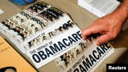 "A Tea Party member reaches for a pamphlet titled ""The Impact of Obamacare"", at a Tea Party Rally in Littleton, New Hampshire, Oct. 27, 2012"