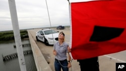 Fire Chief Ann Graham, left, and police officer Thomas Molino III raise a tropical storm warning flag, Sept. 13, 2018, in Isle of Palms, S.C.
