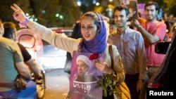 ស្រ្តីម្នាក់កាន់បដារូបប្រធានាធិបតីថ្មីនៃប្រទេសអ៊ីរ៉ង់ Hassan Rouhani ក្នុងយុទ្ធនាការជួបជុំមួយនៅ Tehran អ៊ីរ៉ង់ កាលពីថ្ងៃទី១៧ ឧសភា ២០១៧។