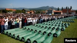 FILE - Bosnian Muslims pray near the coffins of relatives during a funeral for bodies found in a mass grave, in Kozarac, near Prijedor, July 20, 2014.