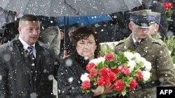 Ðệ nhất phu nhân Ba Lan Anna Komorowska (giữa) đặt vòng hoa trong buổi lễ kỷ niệm 1 năm vụ tai nạn máy bay giết chết cựu Tổng thống Ba Lan Lech Kaczynski và 95 người khác gần thành phố Smolensk của Nga