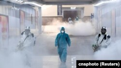 Volunteers in protective suits disinfect a railway station as the country is hit by an outbreak of the new coronavirus, in Changsha, Hunan province, China February 4, 2020.