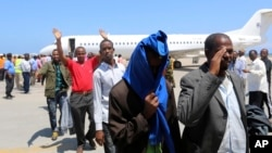 FILE- Deported Somali nationals gesture as they arrive at the airport in Somalia's capital of Mogadishu, April 9, 2014. Sixty-eight Somalis arrived in Magodishu Friday, having been deported by U.S. immigration authorities.