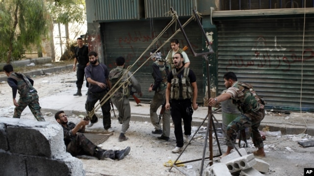 Members of the Free Syrian Army use a catapult to launch a homemade bomb during clashes with pro-government soldiers in the city of Aleppo, October 15, 2012.