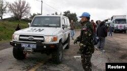 Binh sĩ gìn giữ hòa bình người Philippines đứng bên cạnh một chiếc xe của LHQ trước khi đi từ Israel vào Syria tại biên giới Kuneitra trên Cao nguyên Golan, ngày 5/3/2013.