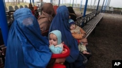 FILE - Afghan refugee women sit with their babies as they wait with others to be repatriated to Afghanistan, at the United Nations High Commissioner for Refugees (UNHCR) office on the outskirts of Peshawar, Feb. 2, 2015.