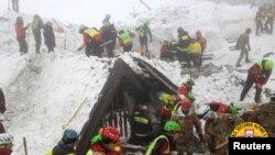 Petugas penyelamat melakukan pencarian korban di sekitar Hotel Rigopiano di Farindola, Italia tengah, yang terkena longsoran salju, 22 Januari 2017.