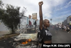 In this Saturday, May 30, 2020 file photo, a protester poses for photos next to a burning police vehicle in Los Angeles during a demonstration over the death of George Floyd. a black man who was killed in police custody in Minneapolis on May 25.
